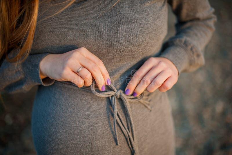 Det gravida anseendet för ung kvinna på stranden i en stucken grå färg klär Isolerat på vit royaltyfri bild