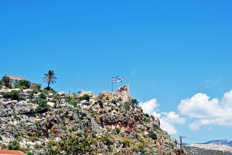 Det grekiska flaggaflyget på överkanten av ett stenigt berg royaltyfri fotografi