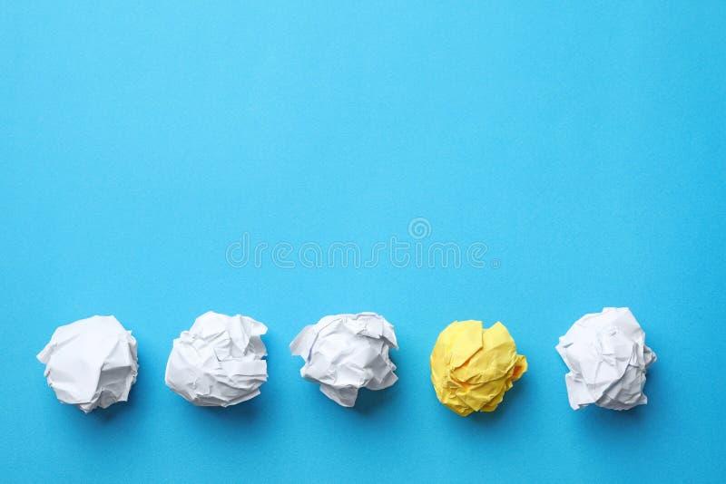 Det gula arket av skrynkligt papper bland vita på färgbakgrund, lägenhet lägger royaltyfria foton