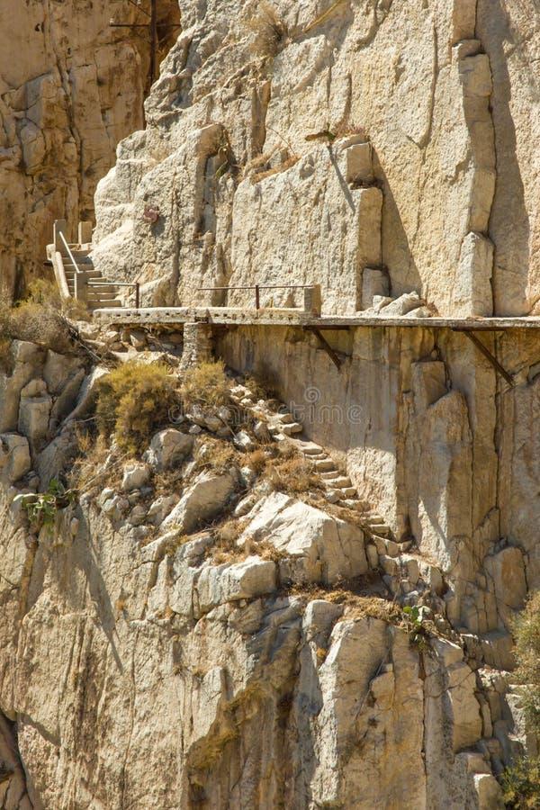 Det gula berget vaggar väggen med rostiga klämmor, El Camino del Rey, royaltyfri fotografi