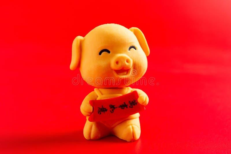 Det gula gulliga svinet som maskot för det nya året 2019 på den röda bakgrundsöversättningen för det kinesiska på engelsk