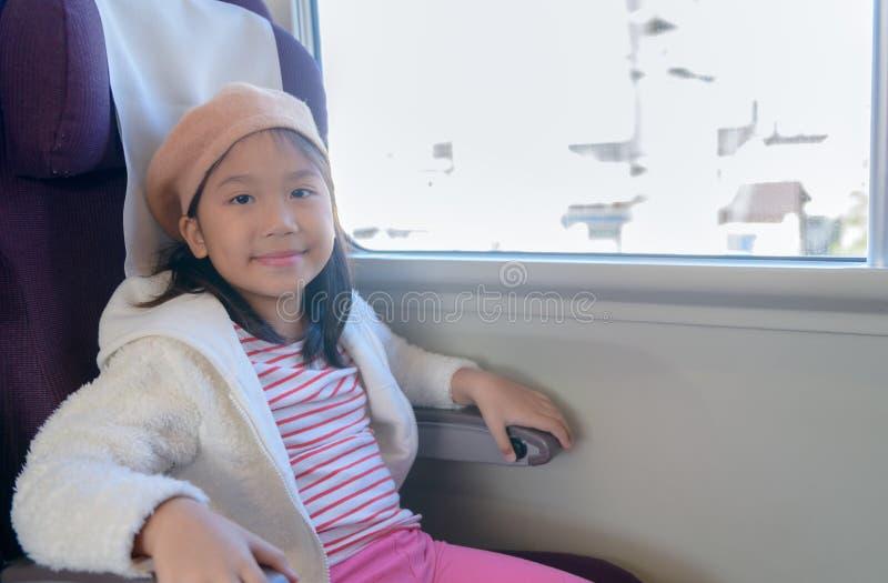 Det gulliga asiatiska flickaleendet och sitter i drevet arkivbilder