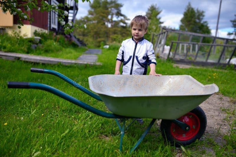 Det gulliga barnet behandla som ett barn pojken nära skottkärran i trädgård royaltyfri fotografi