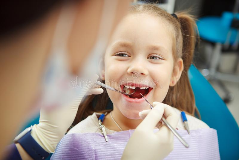 Det gulliga barnet sitter på tandläkarestol med leende fotografering för bildbyråer