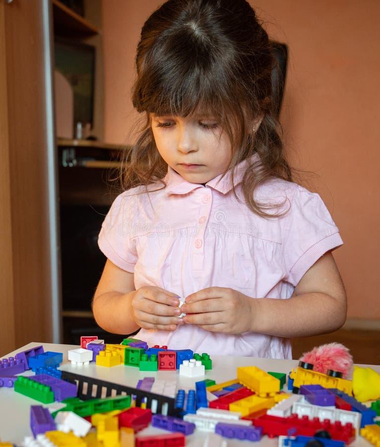 Det gulliga barnet staplar byggnadskuber som sitter på tabellen i barnkammarerum royaltyfria bilder