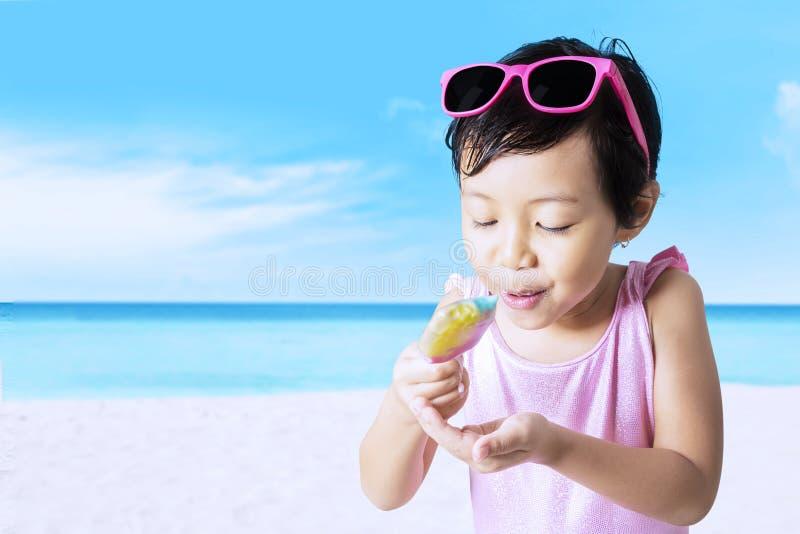 Det gulliga barnet tycker om glass på kusten royaltyfria foton