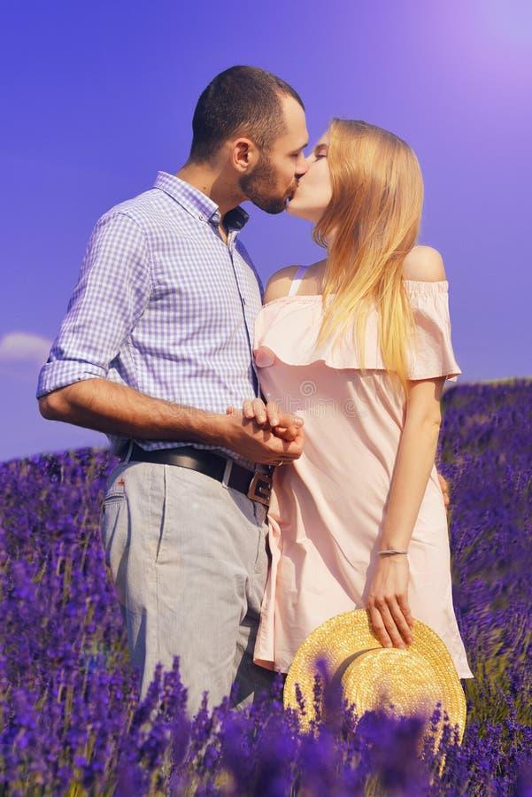 Det gulliga barnparet som är förälskat i ett fält av lavendel, blommar Tyck om ett ögonblick av lycka och förälskelse i ett laven royaltyfri foto