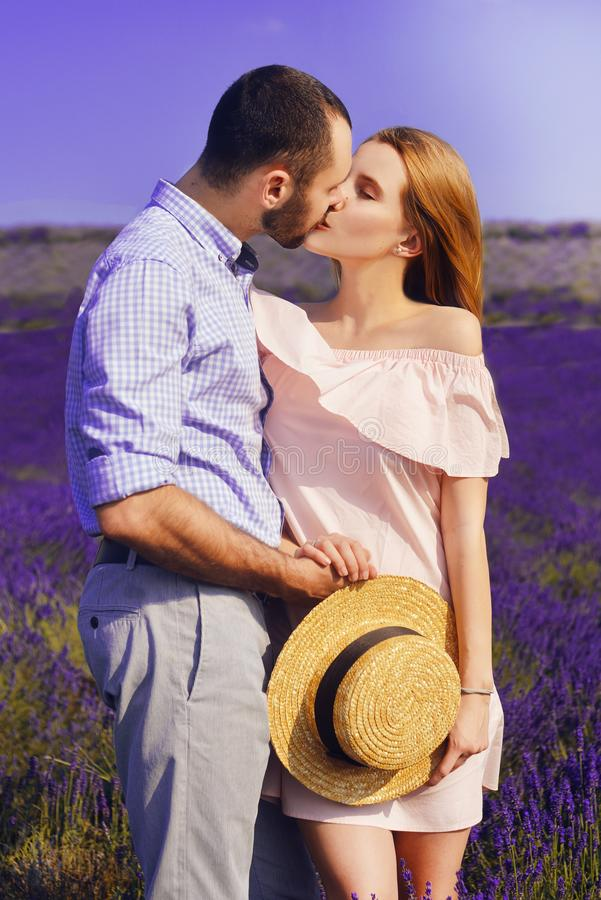 Det gulliga barnparet som är förälskat i ett fält av lavendel, blommar Tyck om ett ögonblick av lycka och förälskelse i ett laven arkivfoto