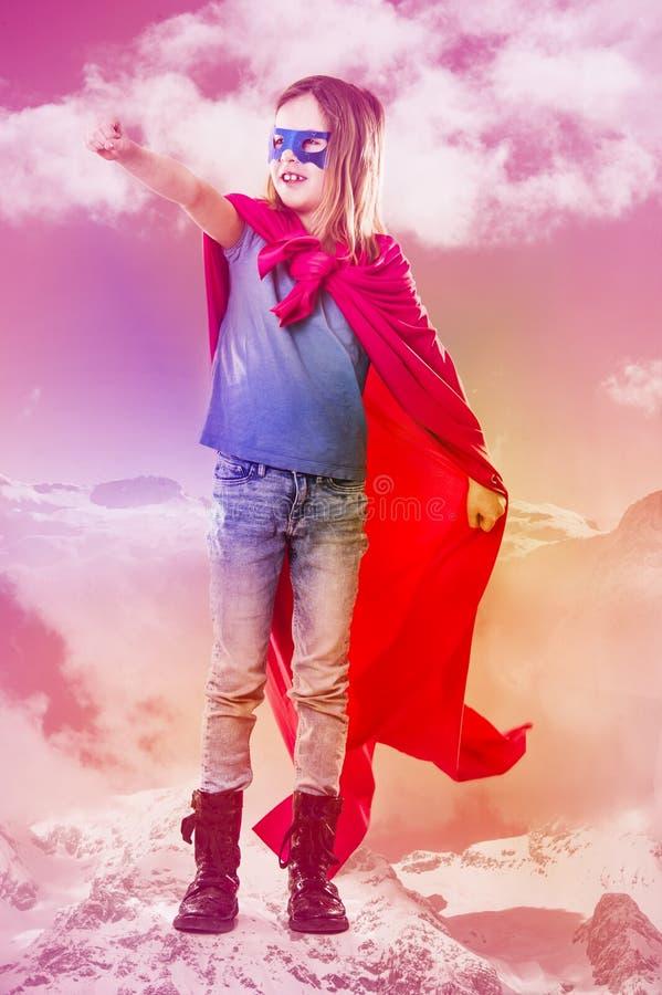 Det gulliga lilla barnet bär en superheromaskeradkläder arkivbild