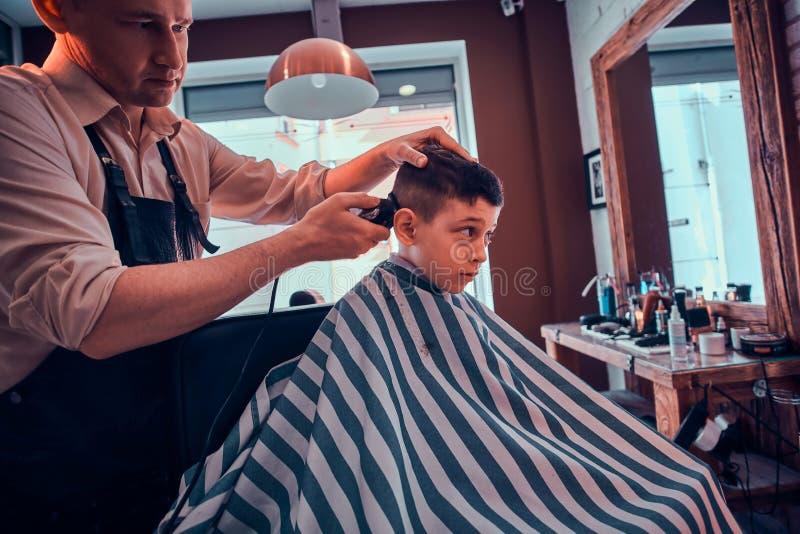 Det gulliga lilla barnet f?r moderiktig frisyr fr?n barberare p? den upptagna frisersalongen royaltyfri fotografi