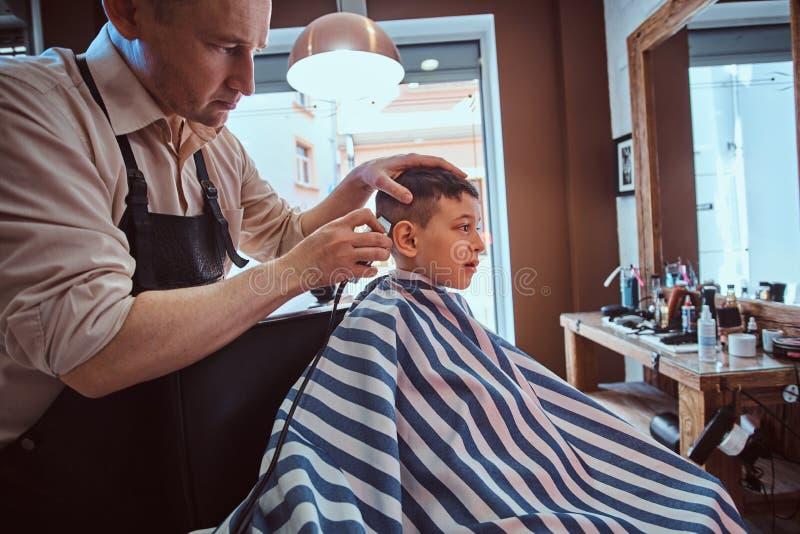 Det gulliga lilla barnet f?r moderiktig frisyr fr?n barberare p? den upptagna frisersalongen royaltyfria foton