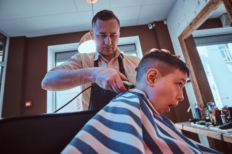 Det gulliga lilla barnet f?r moderiktig frisyr fr?n barberare p? den upptagna frisersalongen fotografering för bildbyråer