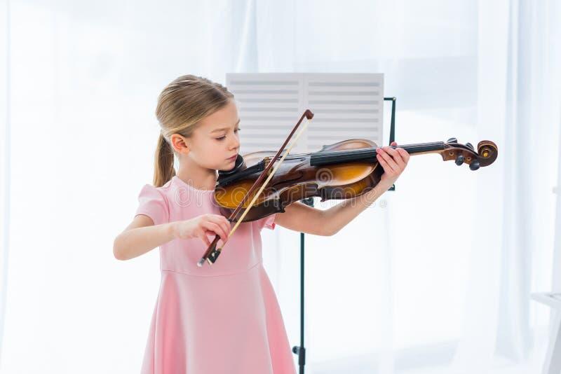 det gulliga lilla barnet i rosa färger klär spela fiolen royaltyfri foto