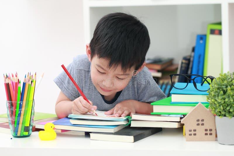 Det gulliga lilla barnet som gör läxa som läser en bokfärgläggning, söker w arkivbilder