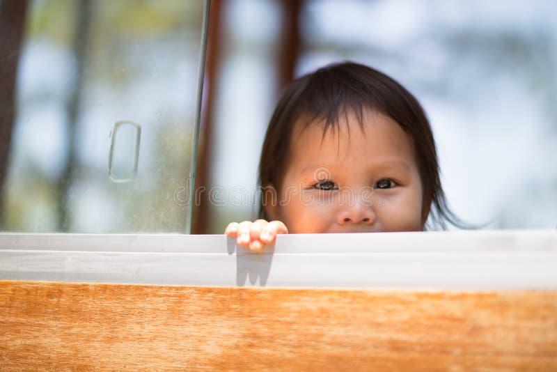 Det gulliga lilla barnet som spelar kurragömma i, parkerar arkivfoto