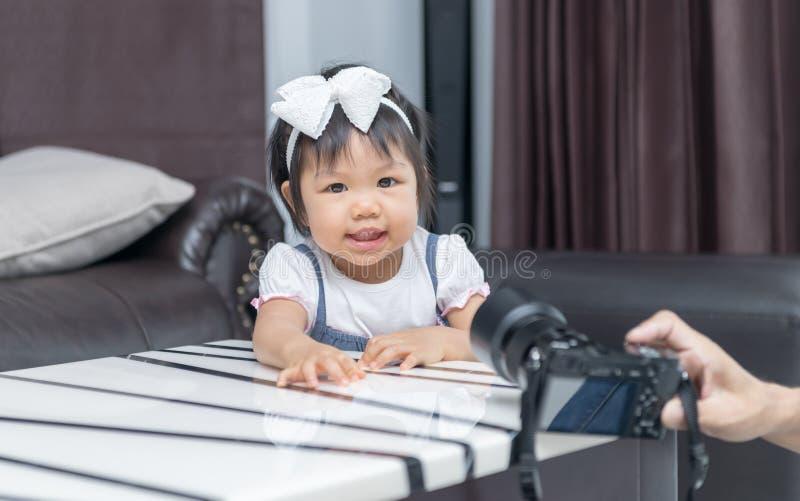 Det gulliga liten flickaleendet och tar bilden royaltyfria bilder