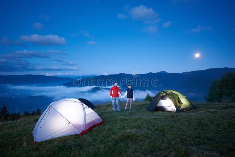 Det gulliga paret står nära campa rymmande händer mot bakgrunden av morgonberglandskap arkivbilder