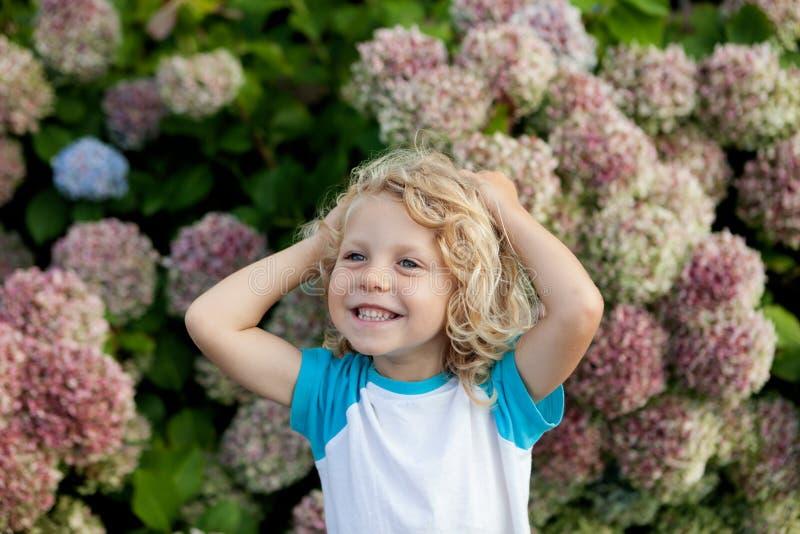 Det gulliga småbarnet med många blommar i trädgården arkivfoton