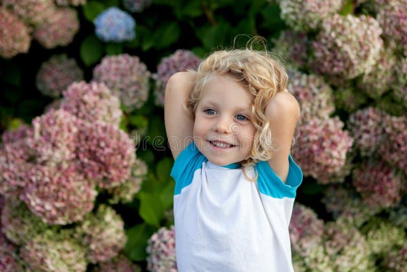 Det gulliga småbarnet med många blommar i trädgården arkivfoto