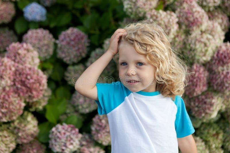Det gulliga småbarnet med många blommar i trädgården royaltyfri fotografi
