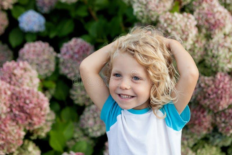 Det gulliga småbarnet med många blommar i trädgården royaltyfri bild