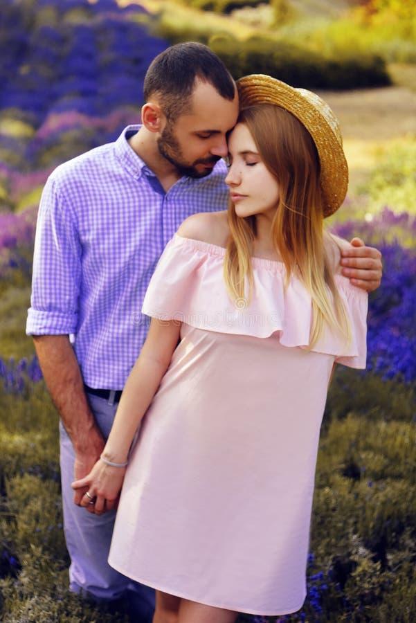 Det gulliga unga lyckliga paret som är förälskat i ett fält av lavendel, blommar Tyck om ett ögonblick av lycka och förälskelse i royaltyfri bild