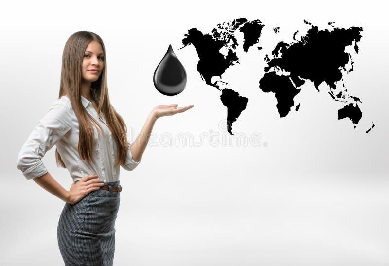 Det härliga affärskvinnaanseendet med stor olje- droppe ovanför hennes öppet gömma i handflatan på vit bakgrund arkivfoton