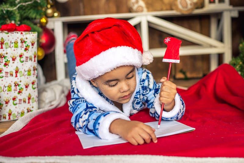 Det härliga afrikanska amerikantsky barnet skrivar ett brev till Santa Claus royaltyfri fotografi