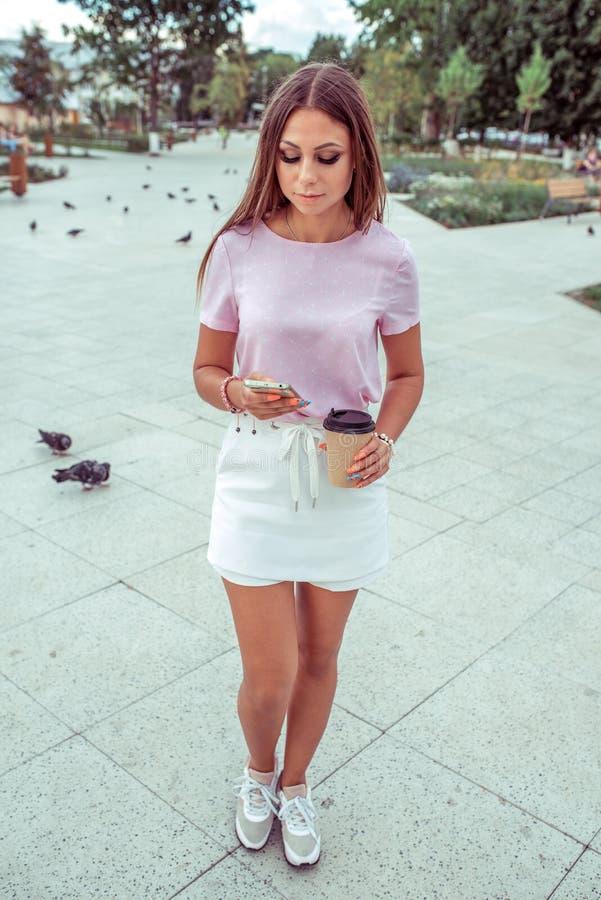 Det härliga anseendet för flickabrunettkvinna parkerar in I sommaren i staden i handen en smartphone och en kopp kaffe arkivbilder