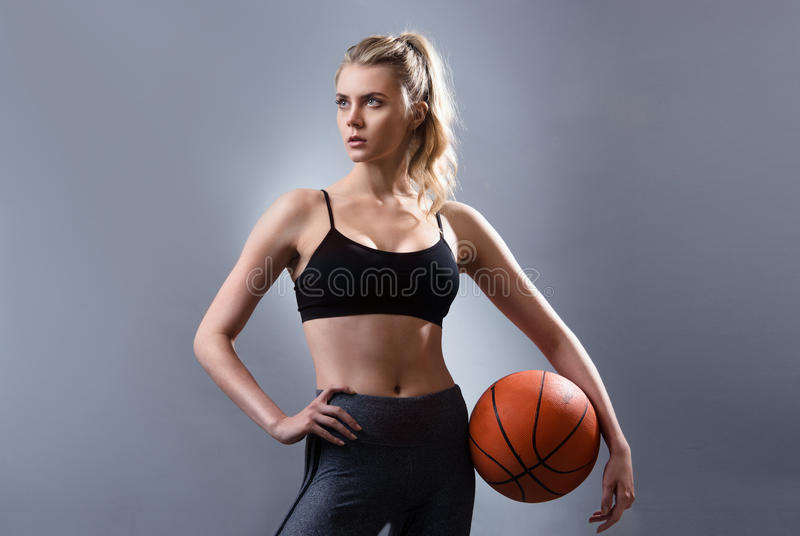 Det härliga anseendet för kvinnabasketspelare och hållande basket klumpa ihop sig arkivbild