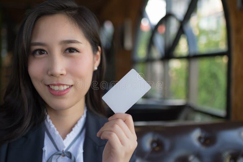 Det härliga asiatiska leendet och håll för affärskvinna förbigår den vita affären eller kreditkorten som isoleras på vit bakgrund royaltyfria bilder