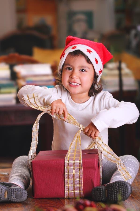 Det härliga barnet öppnar julgåvor arkivbilder