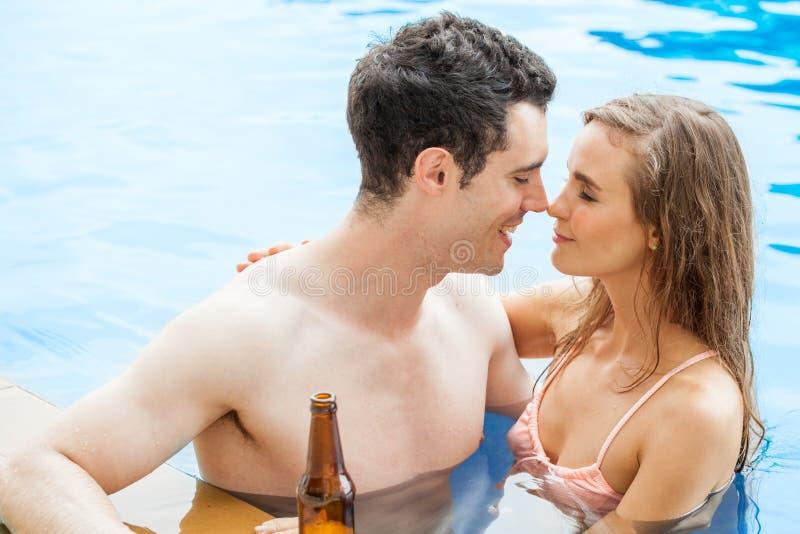 Det härliga barnet kopplar ihop förälskat tillsammans i simbassängen, rubbin royaltyfria foton