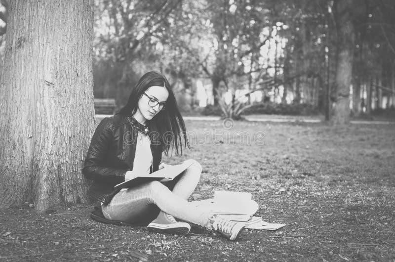 Det härliga barnet skolar eller högskolaflickan med långa hår- och ögonexponeringsglas som sitter på jordningen i parkera som läs fotografering för bildbyråer
