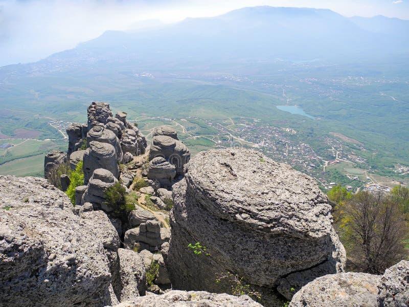 Det härliga berglandskapet med rundat vaggar Bästa sikt av den bebodda dalen med sjön Avlägsna bergplatår i en blått royaltyfri bild