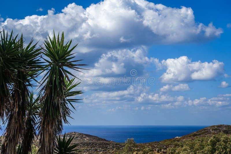 Det härliga blåa havet bak bergen och den härliga blåa himlen med många vita moln arkivfoto