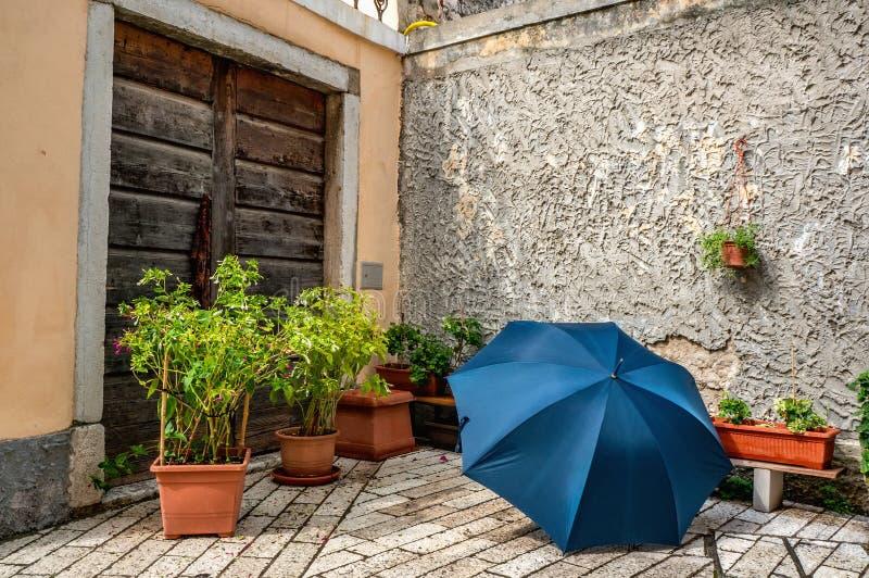 Det härliga blåa paraplyet ligger på kullerstarna bland blommorna på bakgrunden av stenväggar Design och landskap av royaltyfri bild