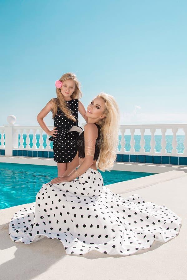 Det härliga blonda barnet fostrar, och dottern, iklädd prickar klär arkivfoton