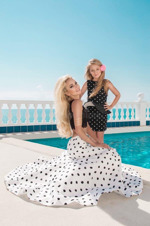 Det härliga blonda barnet fostrar, och dottern, iklädd prickar klär arkivfoto
