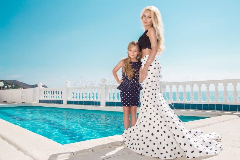 Det härliga blonda barnet fostrar, och dottern, iklädd prickar klär arkivbilder