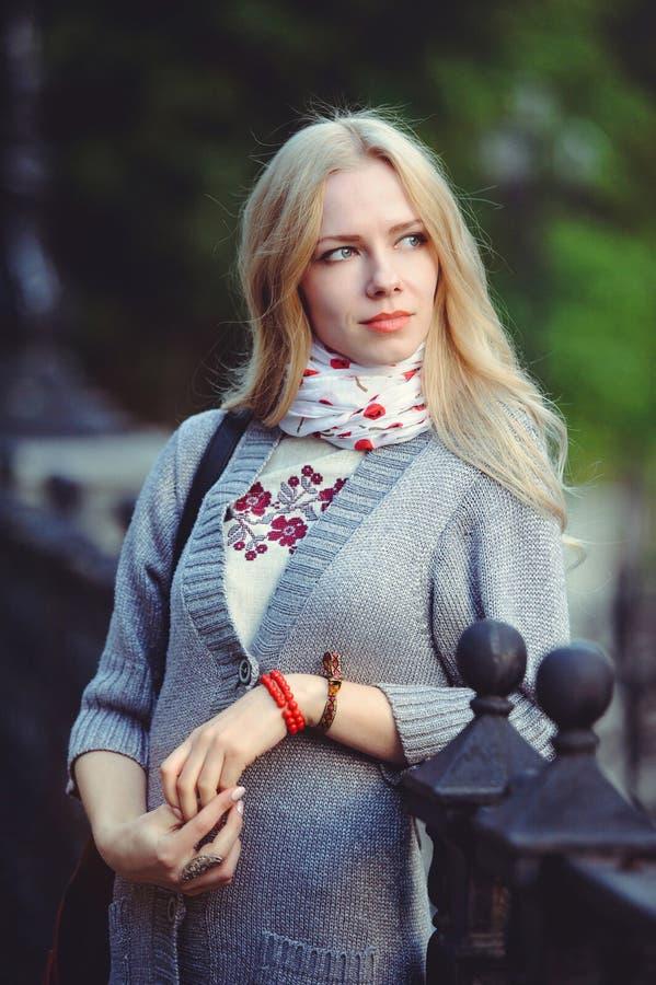 Det härliga blonda kvinnaanseendet i staden på den iklädda natten en vit klänning och en tröja på hennes halshalsduk som är blygs arkivbilder