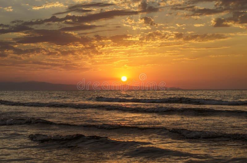 Det härliga flammande solnedgånglandskapet på Kaspiska hav- och apelsinhimmel ovanför det med guld- reflexion för enorm sol på st arkivbild