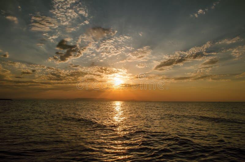 Det härliga flammande solnedgånglandskapet på Kaspiska hav- och apelsinhimmel ovanför det med guld- reflexion för enorm sol på st arkivbilder