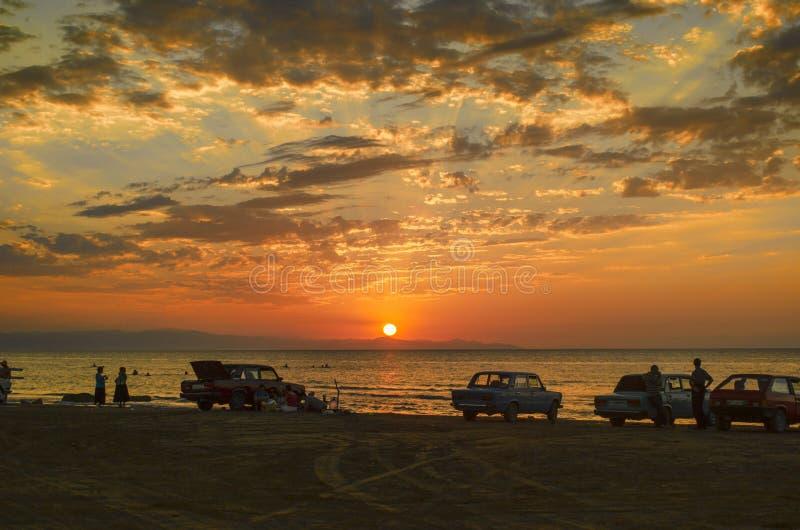 Det härliga flammande solnedgånglandskapet på Kaspiska hav- och apelsinhimmel ovanför det med guld- reflexion för enorm sol på st royaltyfria foton