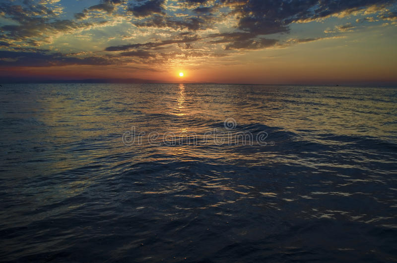 Det härliga flammande solnedgånglandskapet på Kaspiska hav- och apelsinhimmel ovanför det med guld- reflexion för enorm sol på st arkivfoto