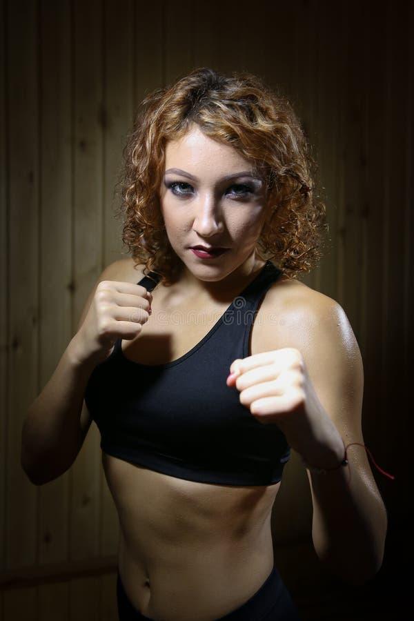 Det härliga flickakämpeanseendet poserar in av boxare i bastu royaltyfria foton