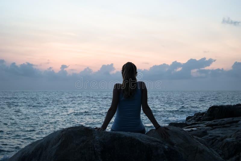 Det härliga flickasammanträdet på stenar och se i ett avstånd, flickan på solnedgången för att meditera i tystnad, härlig kropp B royaltyfri foto