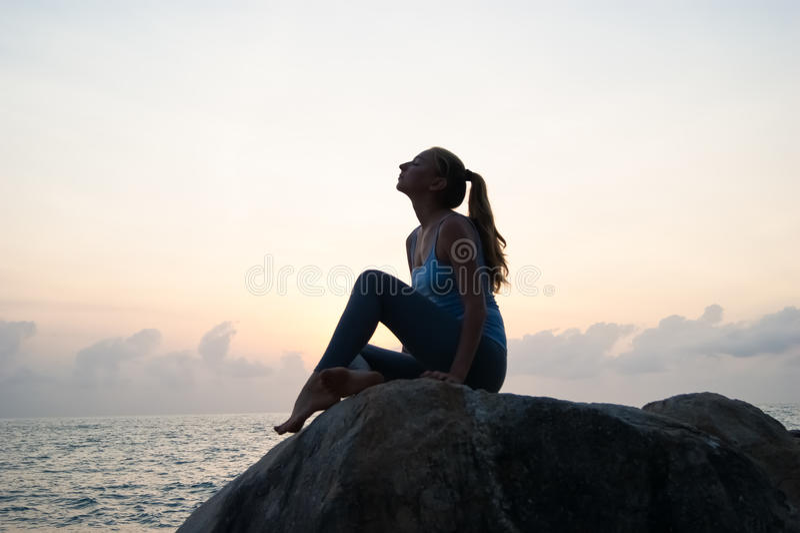 Det härliga flickasammanträdet på stenar och se i ett avstånd, flickan på solnedgången för att meditera i tystnad, härlig kropp B royaltyfria bilder