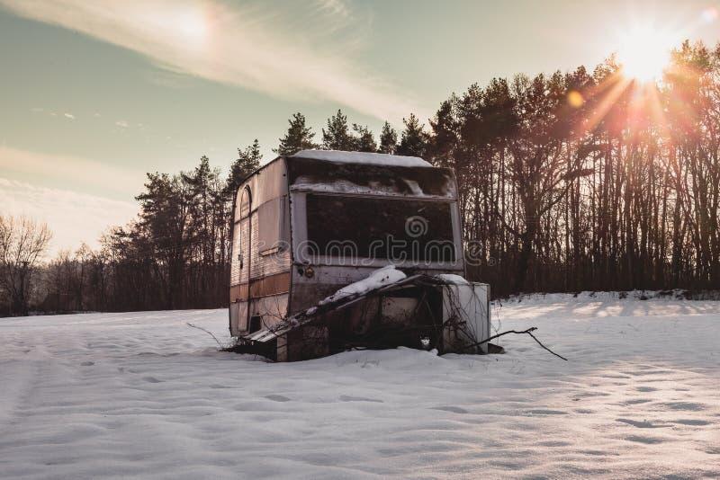 Det härliga fotoet av den gamla och övergav husvagnen i mitt av snö täckte ängen i vintertid Campervan upplyst husvagn royaltyfri fotografi