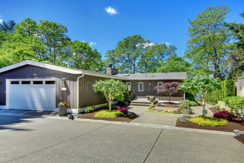 Det härliga hemmet med garage, laken beskådar, och stort bekläda gården. arkivbilder